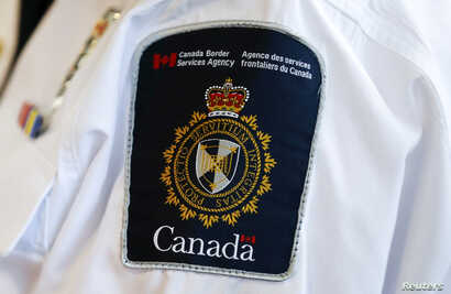 FILE - A Canada Border Services Agency logo is seen on a worker during a tour of the Infield Terminal at Toronto Pearson International Airport in Canada on Dec. 8, 2015.
