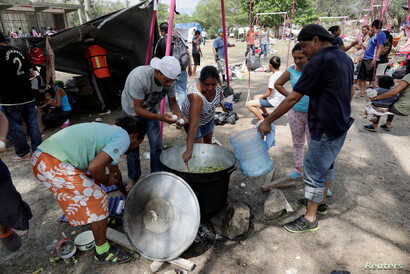 Central American migrants prepare food as they take a break from traveling in their caravan on their journey to the U.S., in Matias Romero, Oaxaca, Mexico, April 3, 2018.