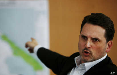 FILE - Pierre Kraehenbuehl, then the operations director of the international Red Cross (ICRC), points to a map during a press conference in Geneva, Switzerland, April 21, 2009.