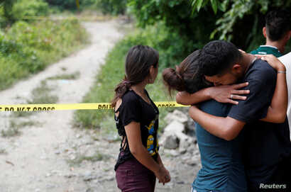 The friends of two men who were killed in gang violence cry at the crime scene in San Pedro Sula, Honduras, July 24, 2018.