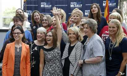 FILE - Rep. Martha McSally, R-Ariz., third from left, laughs as she gets her arm raised by former Arizona Republican Gov. Jan Brewer, third from right, as they pose for a photograph with members of the Women's Coalition after a news conference at a c...