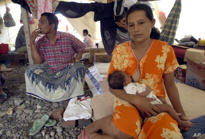 Barunah breastfeeds her 17 days-old baby, Muhammad Rizky in Banda Aceh, Indonesia on Feb. 4, 2005.