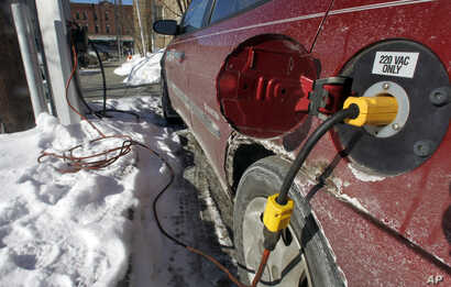 FILE - An electric car is charged in Montpelier, Vt., Jan. 18, 2013. With gas prices low, consumers are buying more trucks and SUVs and fewer fuel-efficient vehicles. That makes it harder to reach fleetwide gas mileage targets.