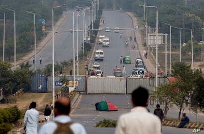 Authorities place shipping containers to stop protesters at an entrance to the capital center following a court decision in favor of a Christian woman in Islamabad, Pakistan, Nov. 1, 2018.