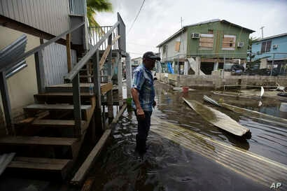 Juana Matos resident Hector Rosa walks through a flooded area after the passing of Hurricane Maria, in Puerto Rico, Wednesday, September 27, 2017. Since the devastating impact of said hurricane, the supply line of goods in general was interrupted in ...