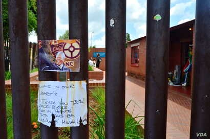A card and note hang on the fence surrounding the Nelson Mandela National Museum, Mandela's former home, in Soweto, Dec. 12, 2013. (Peters Cox for VOA)