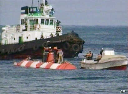 FILE - Crew members of a Russian minisubmarine and rescue team members stand on its hull (white and red streaks) shortly after the sub surfaced in the Beryozovaya Bay about 15 kilometers (10 miles) off the Kamchatka coast, Aug. 7, 2005, in this image...