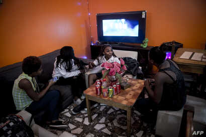 A group of young Haitian migrants gather to talk at a Haitian restaurant in the commune of Quilicura in Santiago. April 24, 2018.