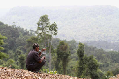 FILE - A man smokes before a commemoration ceremony in Koh Kong province May 11, 2012. About three hundred people traveled to the Cardamom Mountains in Koh Kong province, in Southwestern Cambodia, to investigate alleged illegal logging and commemorat...