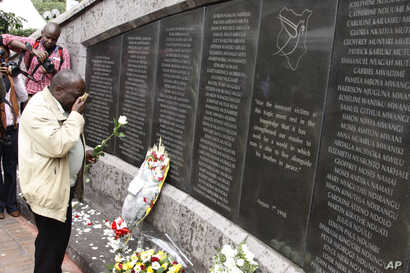 FILE - An unidentified man lays flowers at the US Embassy bombing memorial site in Nairobi, Kenya, Aug. 7, 2013.