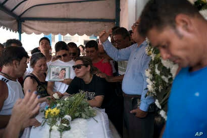 Carla Cristina Santos grieves over the coffin holding her 22-year-old son Matheus Lessa in Rio de Janeiro, Brazil, Jan. 17, 2019. Lessa was shot and killed while trying to protect his mother during a robbery in their family-owned store.