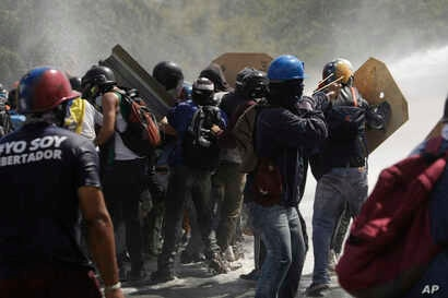 Anti-government protesters clash with riot police, encountering water cannon spray, during a march toward the Ombudsman's Office in Caracas, Venezuela, May 29, 2017.