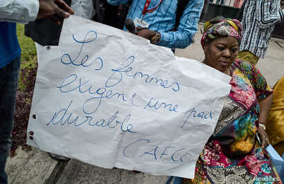 "A Congolese woman holds a placard reading ""Women require stable peace"" as she and others sit in protest outside talks between the opposition and the government of President Joseph Kabila at the Conference episcopale nationale du Congo (CENCO) headqua..."