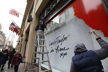 Workers scrape a sign off a display window outside Lord & Taylor's flagship Fifth Avenue store after it closed for good mid-afternoon, Jan. 2, 2019, in New York.