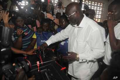 Former soccer star George Weah, presidential candidate for the Coalition for Democratic Change casts his vote during a presidential election in Monrovia, Liberia, Oct. 10, 2017.