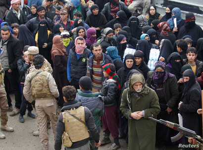 FILE - Displaced Iraqis from Mosul, who are fleeing from Islamic State militants, gather to receive aid in the east of Mosul, Iraq, Dec. 21, 2016.