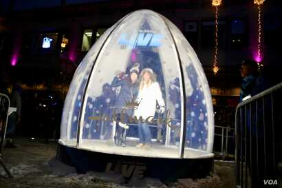 Fans at Super Bowl Live in Minneapolis, Minnesota, pose inside of a live-sized snow globe.
