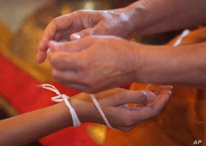 A Buddhist monk ties a holy thread to a member of Wild Boars soccer team for good luck after marking the completion of their serving as novice Buddhist monks. The boys served as novice monks to give thanks for their survival and to show their gratitu...