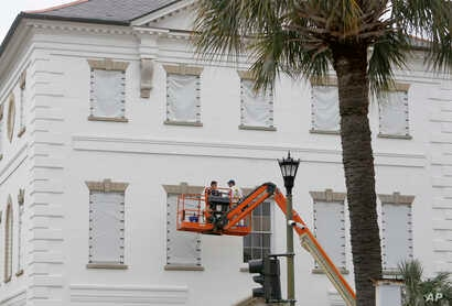 Workers cover the windows of the historic Charleston County Courthouse in Charleston, South Carolina, in preparation for the advancing Hurricane Florence, Sept. 11, 2018.