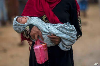 FILE - A Rohingya Muslim woman, who crossed over from Myanmar into Bangladesh, holds her sick daughter and some medicine and walks back toward her shelter in Thaingkhali refugee camp, Bangladesh, Oct. 21, 2017.