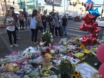 Route 91 Festival goers, tourists and residents of Las Vegas placed candles, flowers, banners and photos of their loved ones at the shrine on the median just across the street from shooting site at the country music festival.
