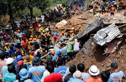 Rescuers search for people trapped in a landslide caused by Typhoon Mangkhut at a small-scale mining camp in Itogon, Benguet, in the Philippines, Sept. 17, 2018.