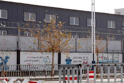 """FILE - In this Dec. 5, 2018, two layers of barbed wire fencing ring the """"Hotan City apparel employment training base"""" where clothing manufacturer Hetian Taida has a factory in Hotan in western China's Xinjiang region."""