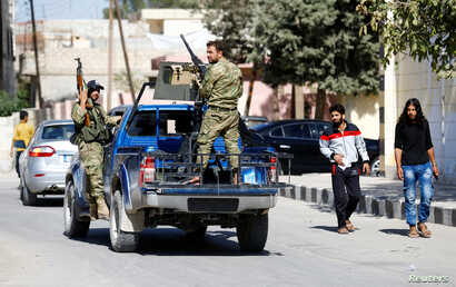 FILE - Members of Turkish-backed Free Syrian Army (FSA) patrol in the border town of Jarablus, Syria.