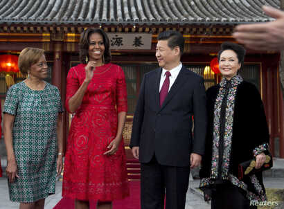 U.S. first lady Michelle Obama, her mother Marian Robinson (L), share a light moment with Chinese President Xi Jinping, and his wife Peng Liyuan (R) after a photograph session at the Diaoyutai State guest house in Beijing, March 21, 2014.