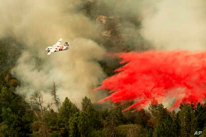 An air tanker drops retardant while fighting to stop the Ferguson Fire from reaching homes in the Darrah community of unincorporated Mariposa Count, Calif., July 25, 2018.