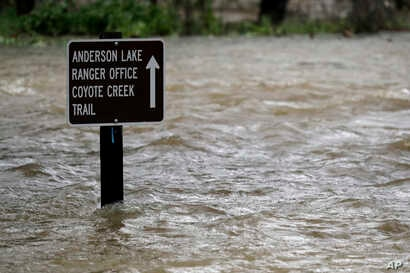 FILE - A sign is submerged in the water from Coyote Creek, Feb. 21, 2017, in Morgan Hill, Calif. Rains have saturated once-drought stricken California but have created chaos for residents hit hard by the storms.