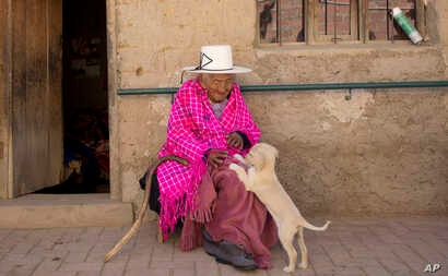 Julia Flores Colque, 117 years old, plays with Chiquita, one of the family pet dogs, while sitting outside her home in Sacaba, Bolivia, Aug. 23, 2018.