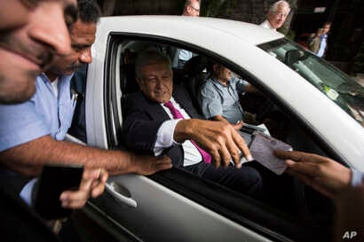 In this July 11, 2018 photo, Mexico's President-elect Andres Manuel Lopez Obrador receives a note from a man, as he leaves his headquarters in the Roma neighborhood of Mexico City.