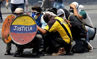 """FILE - Opposition supporters use a shield that reads """"Justice"""" as they clash with security forces during a rally against Venezuela's President Nicolas Maduro in Caracas, Venezuela, April 26, 2017."""