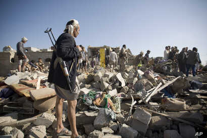 A Houthi Shiite fighter stands guard as people search for survivors under the rubble of houses destroyed by Saudi airstrikes near Sanaa Airport, Yemen, Thursday, March 26, 2015