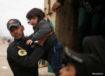An Iraqi soldier helps a displaced child to get out of a truck as Iraqi forces battle with Islamic State militants, in western Mosul, March 28, 2017.