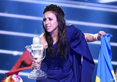 """Ukraine's Jamala celebrates with the trophy after winning the Eurovision song contest final with """"1944"""" in Stockholm, Sweden, May 15, 2016."""