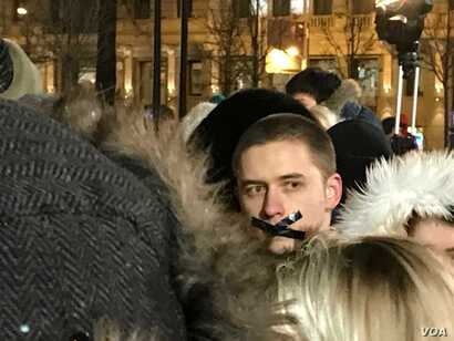 A man in the crowd at a Moscow vigil for those who died in a shopping mall blaze March 25 in the Siberian city of Kemerovo offers an indication of protest, March 27, 2018. Opposition figure Alexei Navalny appeared earlier at the vigil, and there were...