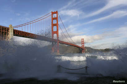 Waves crash against a sea wall in San Francisco Bay beneath the Golden Gate Bridge in San Francisco, California, Dec. 16, 2014.