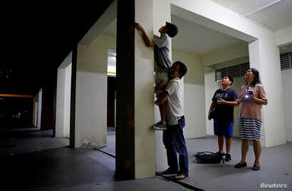 Eric Tan lifts his son Leland, 14, as they try to catch queen ants at a public housing estate in Singapore, May 3, 2017.
