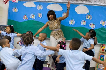 FILE - Former first lady Michelle Obama dances with students at a Washington school that was part of the Turnaround Arts Initiative, May 24, 2013