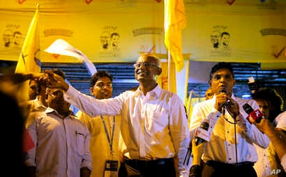 Maldives' opposition presidential candidate Ibrahim Mohamed Solih, center, shakes hands with a supporter as his running mate, Faisal Naseem, right, addresses the gathering in Male, Maldives, Monday, Sept. 24, 2018.