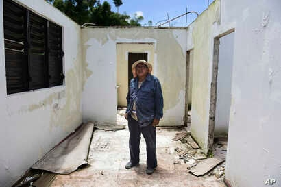 Tinsmith Otoniel Ramos Aponte poses for a portrait, May 16, 2018, inside his mother's home, which lost its roof to Hurricane Maria but did not qualify for federal aid for repair in Yabucoa, a town where many continue without power in Puerto Rico.