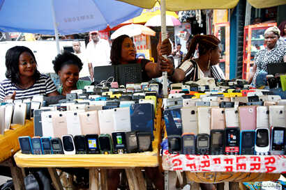 Women vendors display Nokia phone models for sale along with smartphones in Ikeja district in Nigeria's commercial capital Lagos, May 31, 2017.