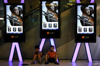 "Children use smartphones near monitors displaying a Chinese action movie ""Wolf Warrior 2"" at a cinema in Beijing, Aug. 10, 2017. The patriotic film reportedly inspired by evacuations of Chinese civilians in Libya and Yemen is becoming one of China's ..."