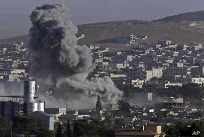 Smoke rises following an airstrike by the US-led coalition aircrafts in Kobani, Syria, during fighting between Syrian Kurds and the militants of Islamic State group, as seen from the outskirts of Suruc, on the Turkey-Syria border, Friday, Oct. 10, 20...