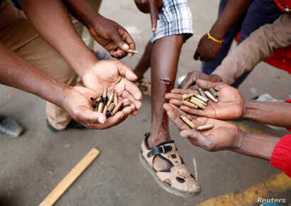 Opposition Movement for Democratic Change supporters hold spent rounds and show injuries after soldiers opened fire outside the party's headquarters in Harare, Zimbabwe, Aug. 1, 2018.