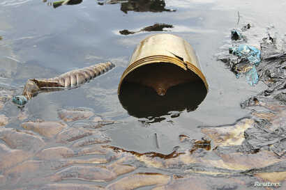 Crude oil from a Shell pipeline spill accumulates along a river bank in the Oloma community in the Niger Delta, Nov. 27, 2014.