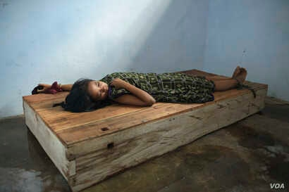 A 24-year-old female resident lies with her wrist and ankle chained to a platform bed at Bina Lestari healing center in Brebes, Central Java. After her husband abandoned her and her 5 year-old daughter to marry someone else, she began to experience d...