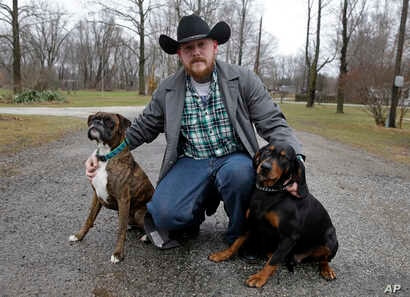 Shane Johnson poses with his dogs outside his home in Tippecanoe, Indiana, Jan. 12, 2017. Johnson was born into extremism. He eventually joined a skinhead group in addition to the KKK but finally decided to quit after getting arrested, stopping drink...